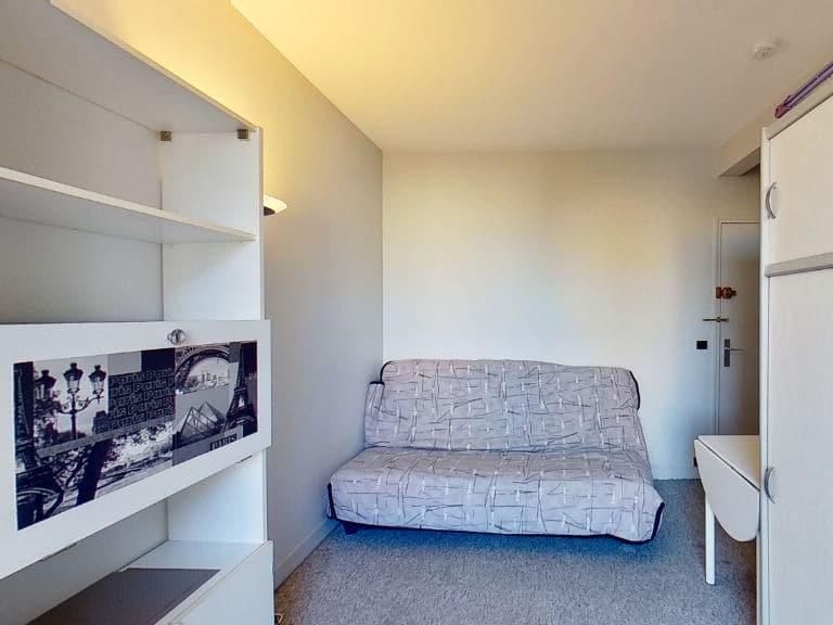 immobilier 94: studio meublé, pièce principale avec canapé, penderie et étagères