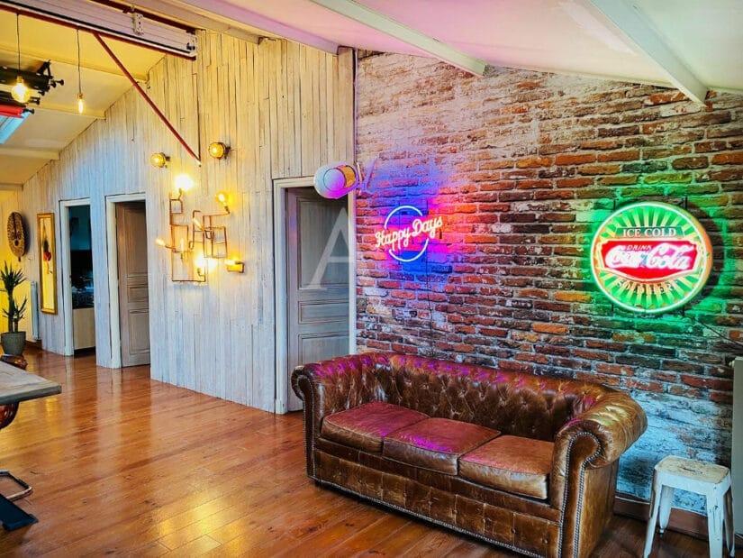 location appartement 94: 4 pièces 144 m², salon avec un mur en brique et lambrie